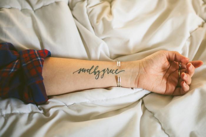 tatouage femme, dessin en encre sur le bras à design mots inspirants, bracelet métallique pour femme