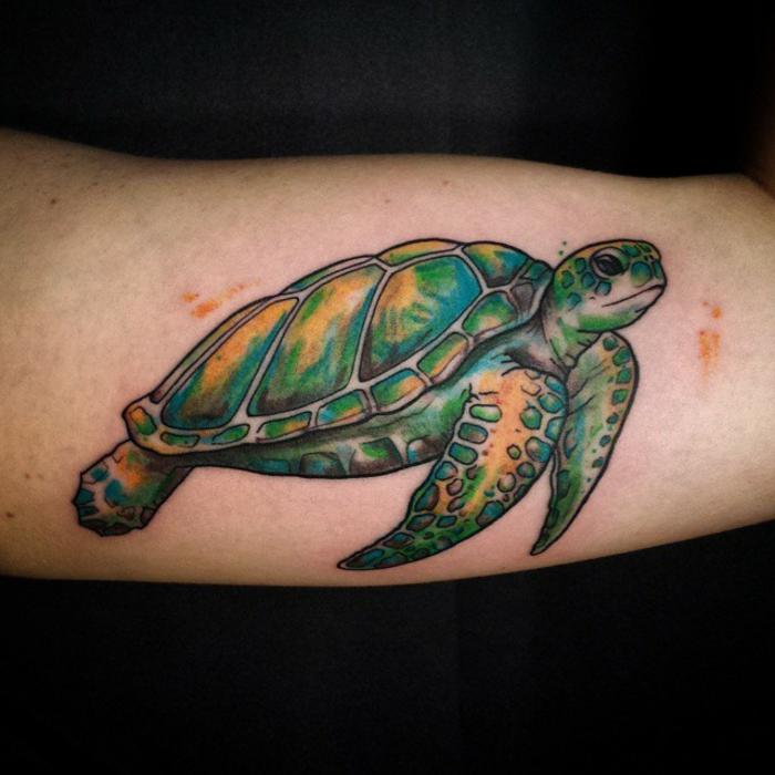 tatouage bras homme, tortue de mer réalistique en couleurs vives sur le bras