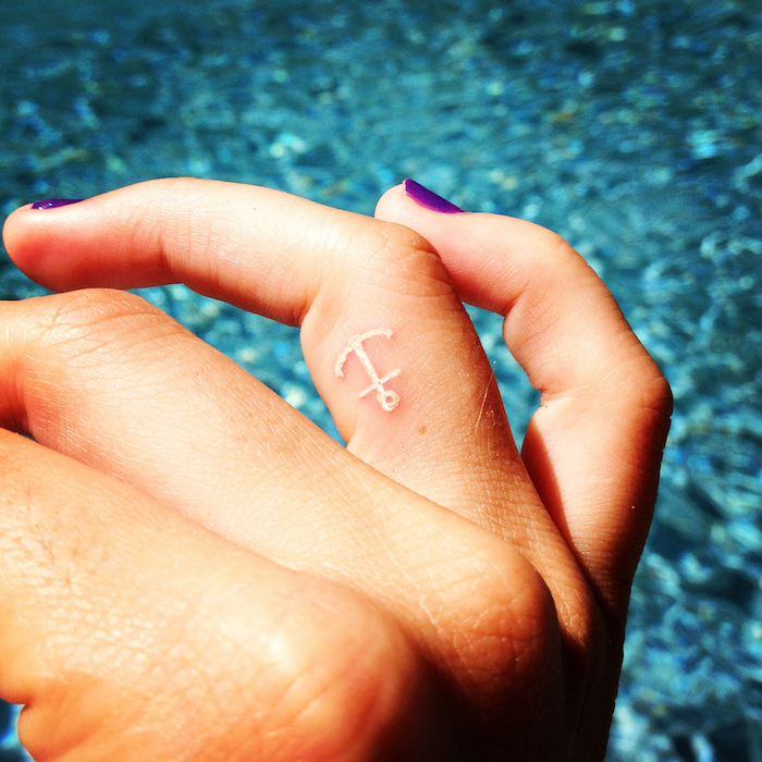 tatouage discret, art corporel sur le doigt, tattoo en blanc à design ancre, nail art violet sur ongles courts