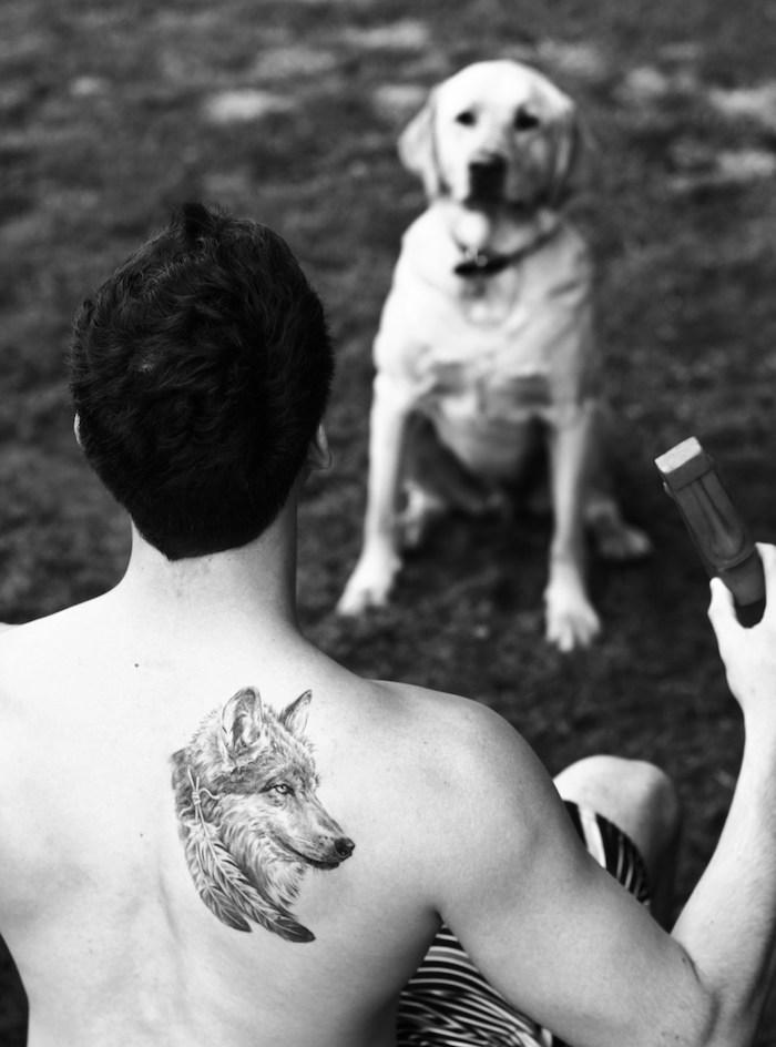 symbole tatouage, homme en promenade avec son chien, tatouage tête de loup sur le dos