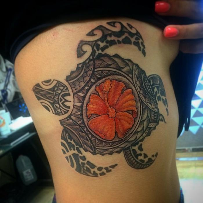 tatouage tortue sur les côtes avec hibiscus orange au centre de sa carapace