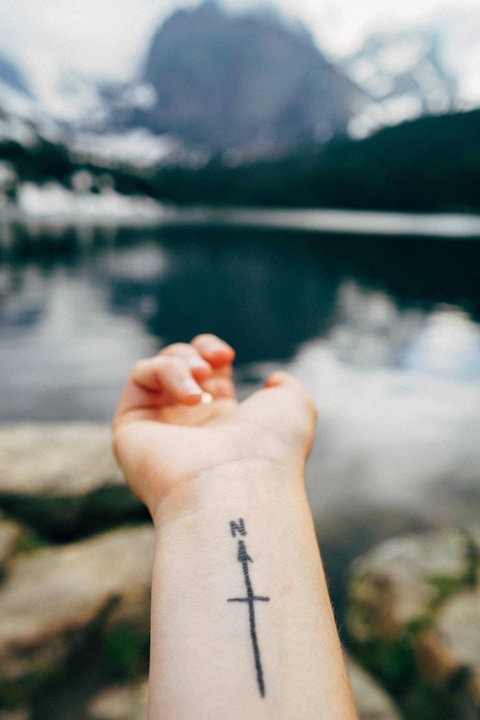 tatouage poignet femme, photo paysage naturel avec sommets de montagne enneigés et lac, main femme