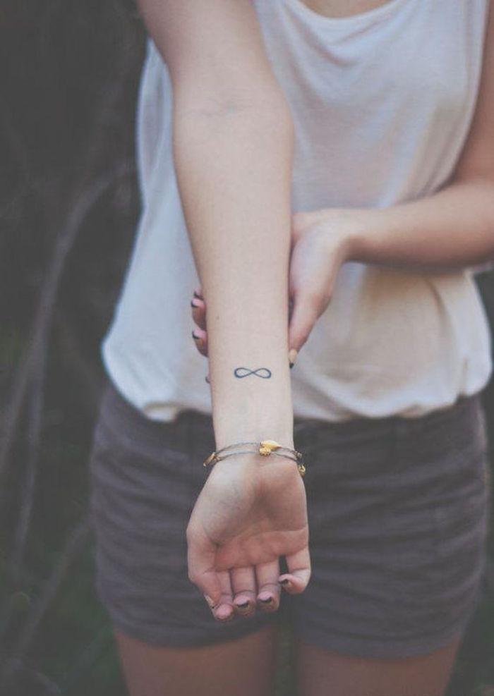 petit tattoo infini discret sur le poignet femme