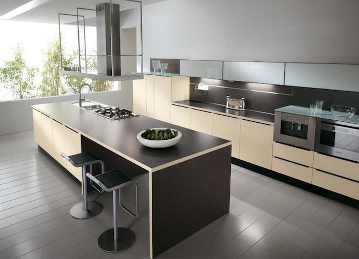 cuisine semi ouverte, ilot central en beige et marron, mur blanc et sol en bois, éclairage sous meubles
