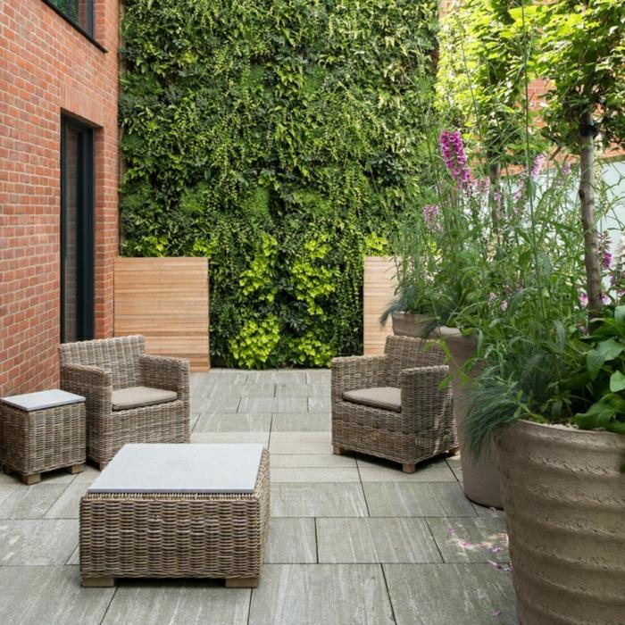 idee salon de jardin tressé, dalles de béton en revêtement, fauteuils et table en rotin, mur végétale plantes vertes