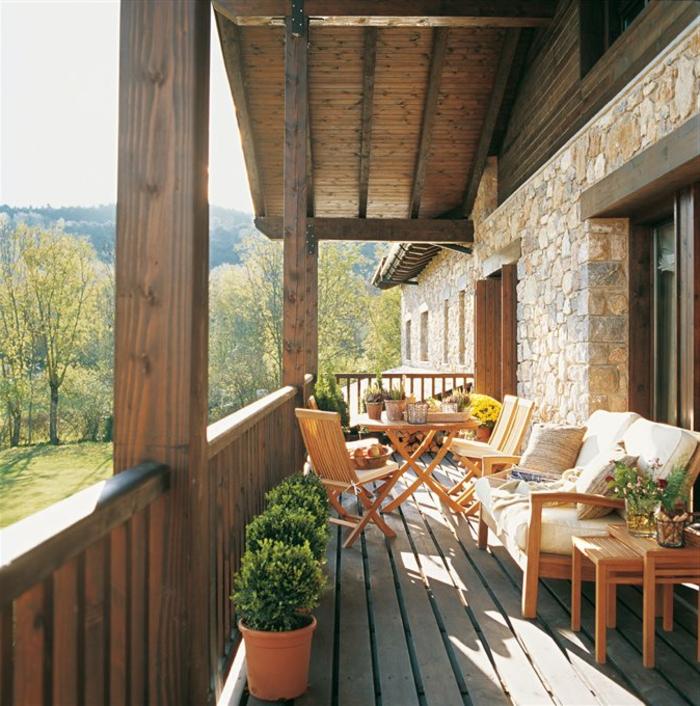 aménager une terrasse en bois, table et chaises, canapé en bois, plantes dans des pots de fleurs, boules buis, mur en pierre