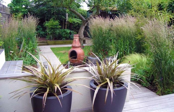 idee terrasse deco en bois et plantes dans des pots de fleurs, arbustes, fleurs, lanterne en cérame marron, arbres