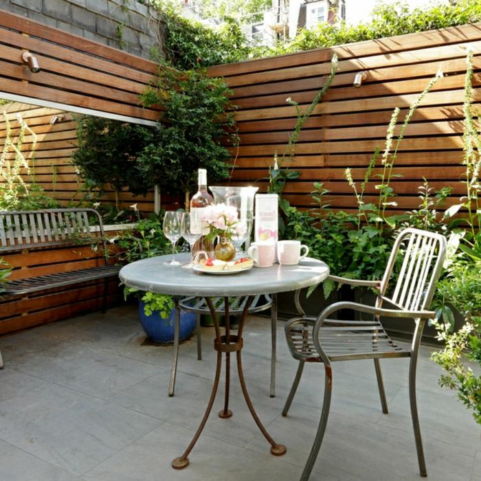 terrasse zen, cloison en bois et carrelage en béton, table, chaise et banc metallique, plusieurs plantes, miroir rectangulaire