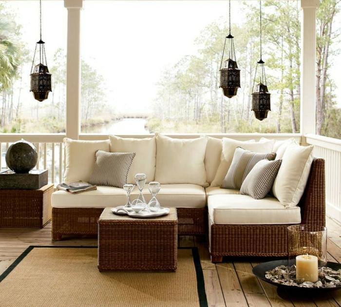 idee salon de jardin tressé, canapé et table en rotin, coussins d assise et décoratifs blancs, suspensions orientales, bougie décorative