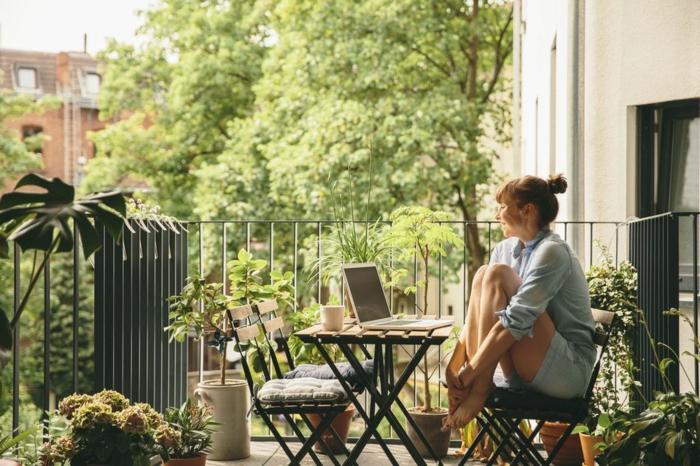 amenagement terrasse zen, coin repas, repos table et chaises en bois et métal, carrelage, plusieurs plantes vertes dans des pots de fleurs