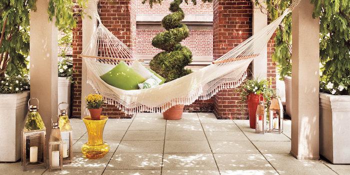amenagement terrasse, revêtement dalles de béton, hamac et coussins blanc et vert, lanternes, arbres dans des bacs à fleurs en béton
