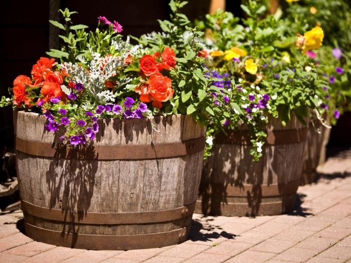 des tonneaux de bois transformés en jardinières fleuries, à l extérieur, exemple idee deco a faire soi meme recup