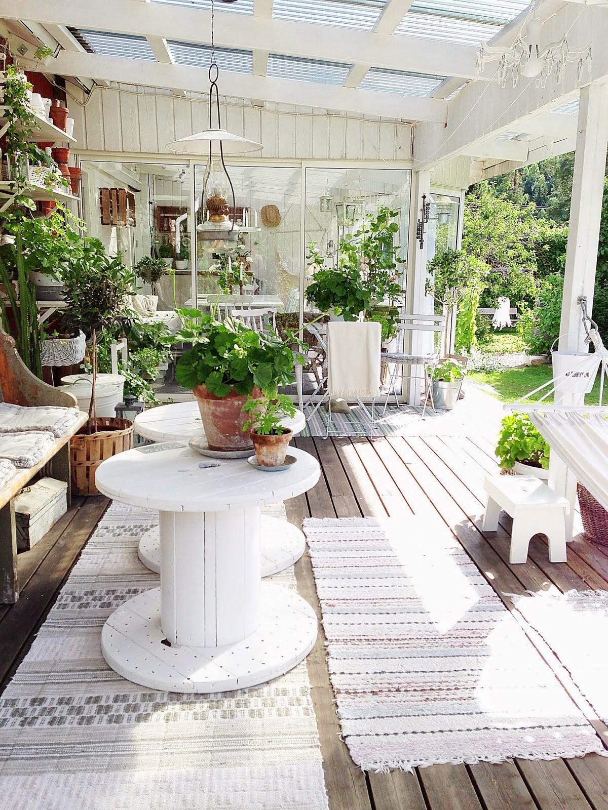 idée de décoration terrasse exterieur avec banc en bois brut et tables en touret blancs, touret bois deco avec beaucoup de plantes vertes