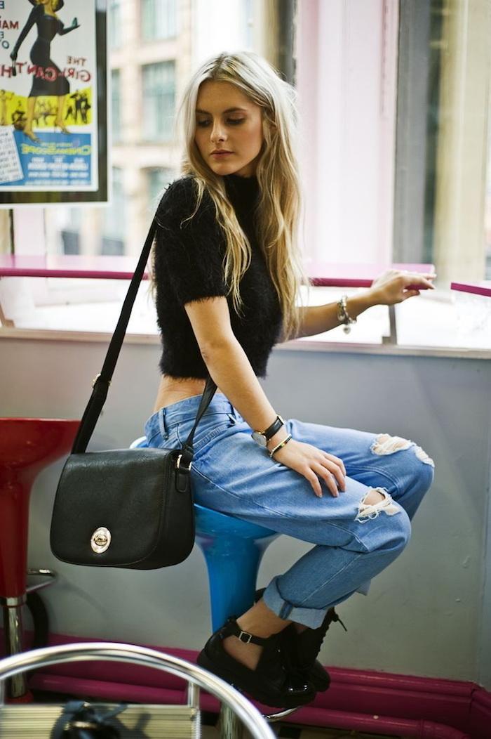 mode femme, paire de jeans déchirés avec top pull en faux fur noir, cheveux longs avec racines noires