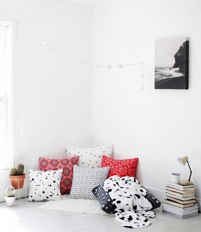 coin detente avec coussin cocooning, plusieurs coussins bohème blanc, noir et rouge, couverture blanche, parquet blanc, pile de livres