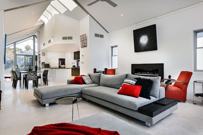 cuisine ouverte sur salon, canapé gris, coussins décoratifs et fauteuil rouge, cheminée noire, façade cuisine blanche coin repas noir et blanc, accord de couleurs
