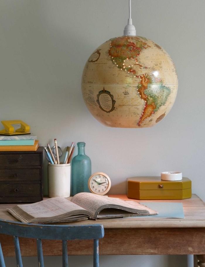 une suspension originale fabriqué à partir un globe terrestre recyclé au-dessus s un bureau et chaise vintage en bois, astuce deco recup