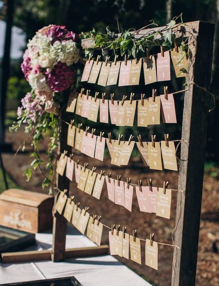 plan de table mariage en grand cadre rustique en bois avec des étiquettes noms invités et nombre table en papier coloré, guirlande verte et bouquet de fleurs colorées