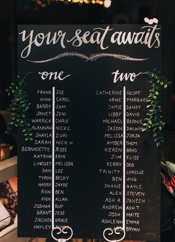 panneau tableau noir avec des noms invités écrits en lettres blanches calligraphiques, plan de table pour mariage esthétique