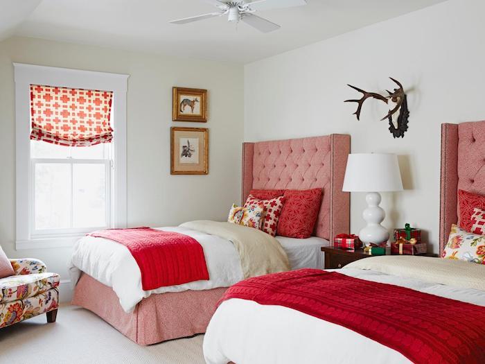 idée deco chambre à coucher avec des lits rose, tête de lit capitonnée, couvertures rouges, coussins colorés, fauteuil à motifs floraux, association de couleur