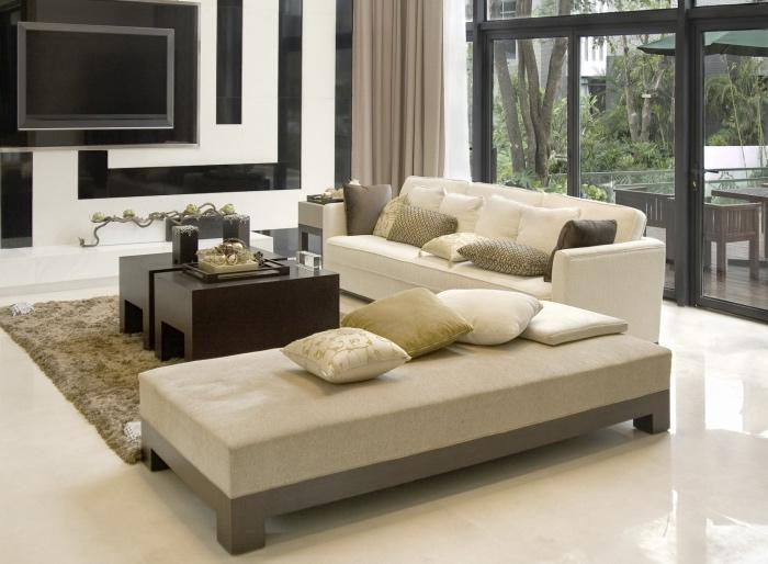 rideaux et chaise longue couleur lin, canapé et sol blanc cassé, table base en bois marron, mur d accent noir et blanc