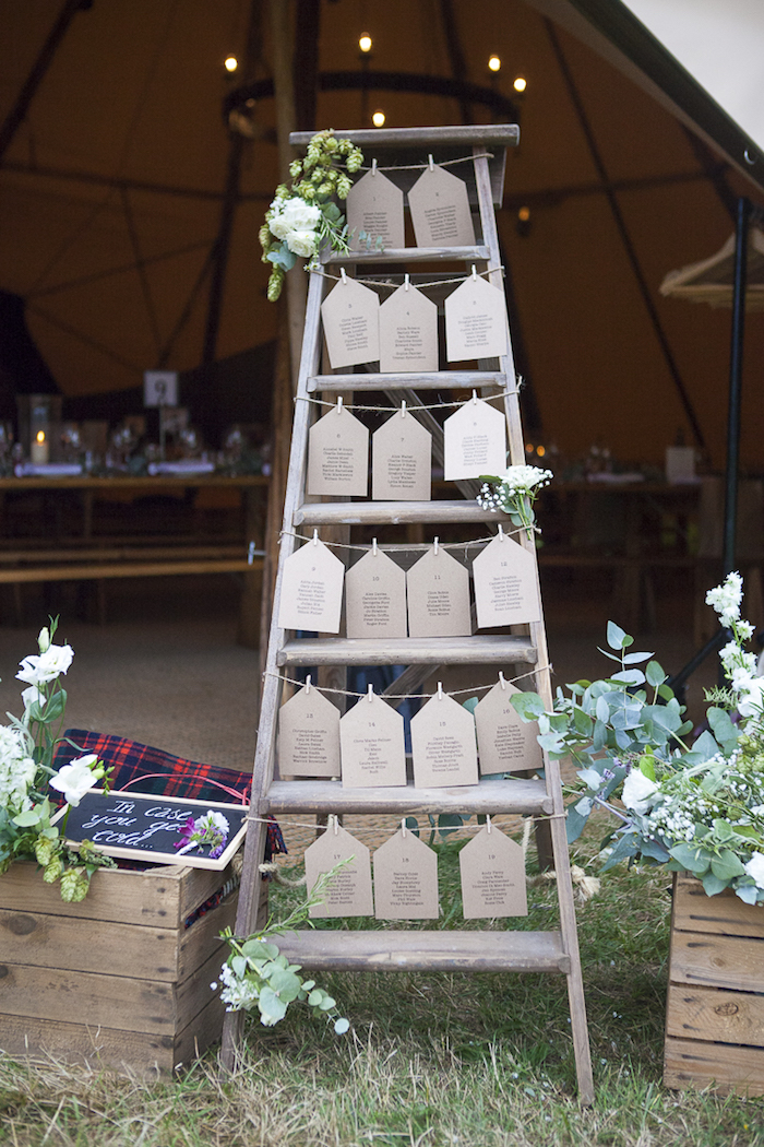 idée de plan de table diy mariage fabriqué à partir une échelle vintage en bois avec des étiquettes listes invités en papier kraft, déco florale, corde de lin et pinces à linge pour suspendre
