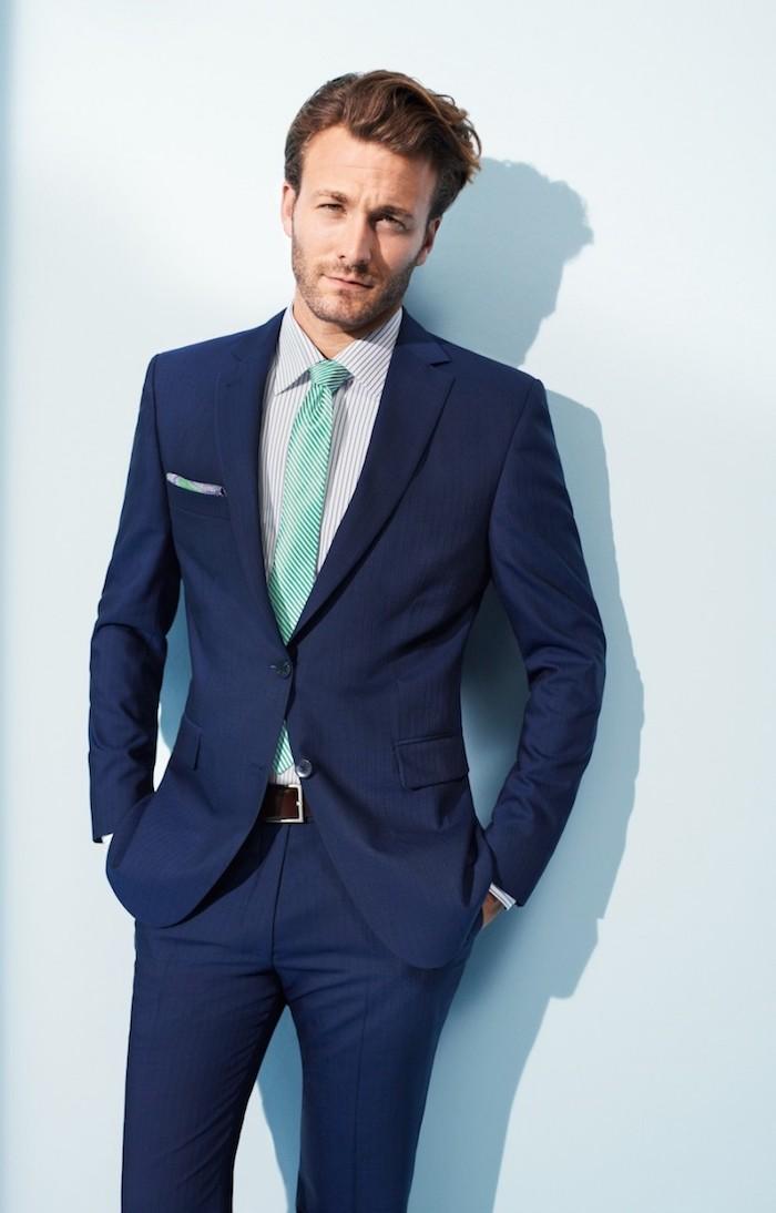 costume bleu marin, coupe de cheveux homme, ceinture marron et cravate verte
