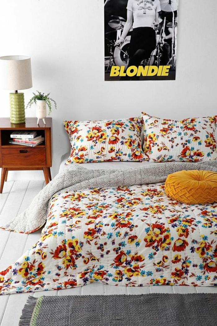 décoration chambre adulte avec lit tout en fleurs en orange et rouge et poster rock