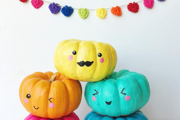 activite halloween, citrouilles repeintes de couleurs diverses, jaune, orange, bleu, avec des dessins de têtes amusantes