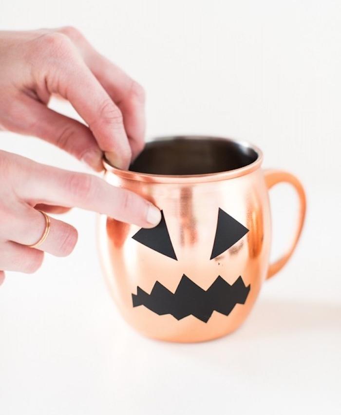 activité manuelle halloween, une tasse à thé couleur rose gold avec des yeux et bouche silhouette noire