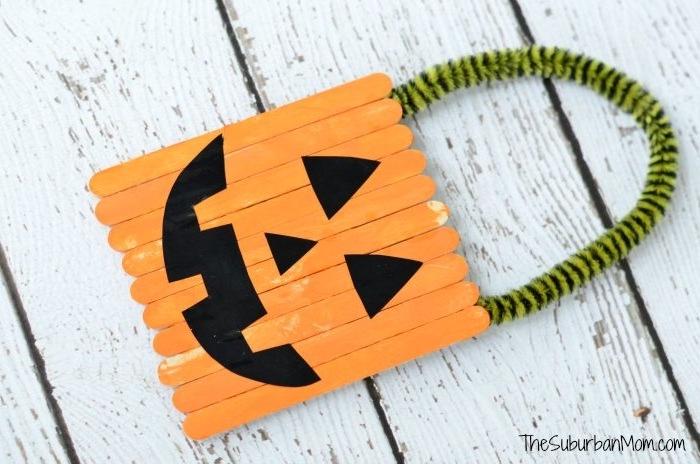 activités manuelles maternelle halloween, bricolage enfant avec des batonnets de glace repeints en orange et traits noirs, manche en cure-pipe