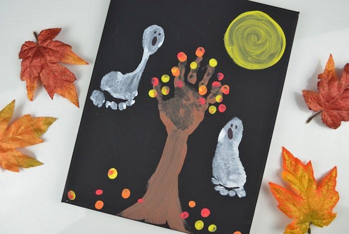 dessin sur une pancarte noire avec arbre empreinte de main et des fantômes empreintes de pieds, lune, feuilles mortes