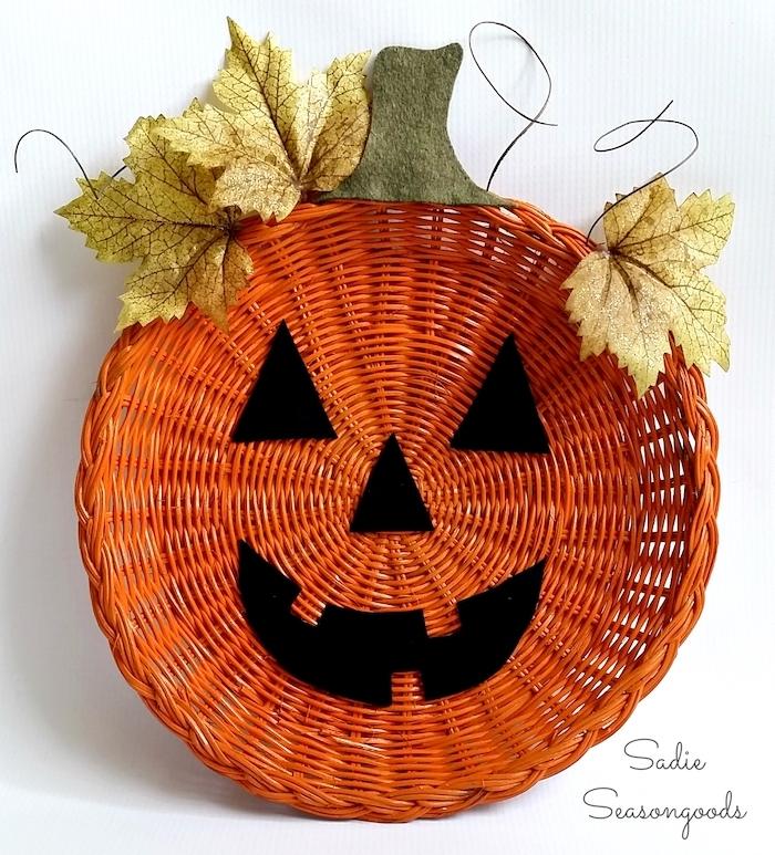 panier en rotin avec des traits de visage jack o lantern en feutrine, des feuilles mortes decoratives, activite manuelle pour halloween