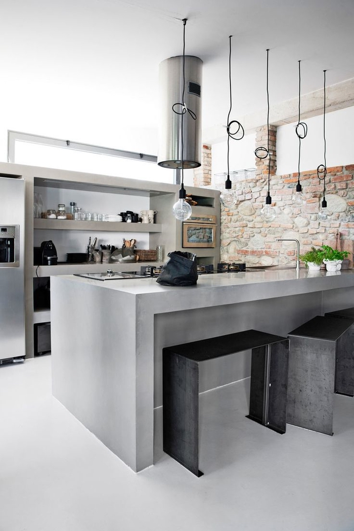 cuisine esprit loft en béton aux accents métalliques et un éclairage industriel caractéristiques pour une deco industrielle
