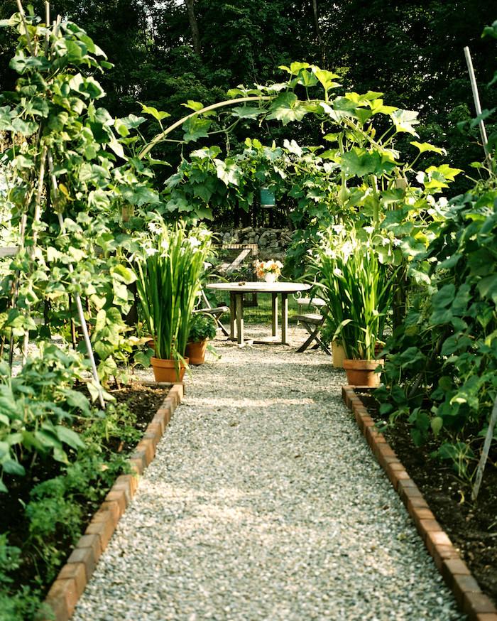 jardin mineral, sentier aux galets et cailloux blancs, bordure de jardin en briques, salon de jardin en bois vintage