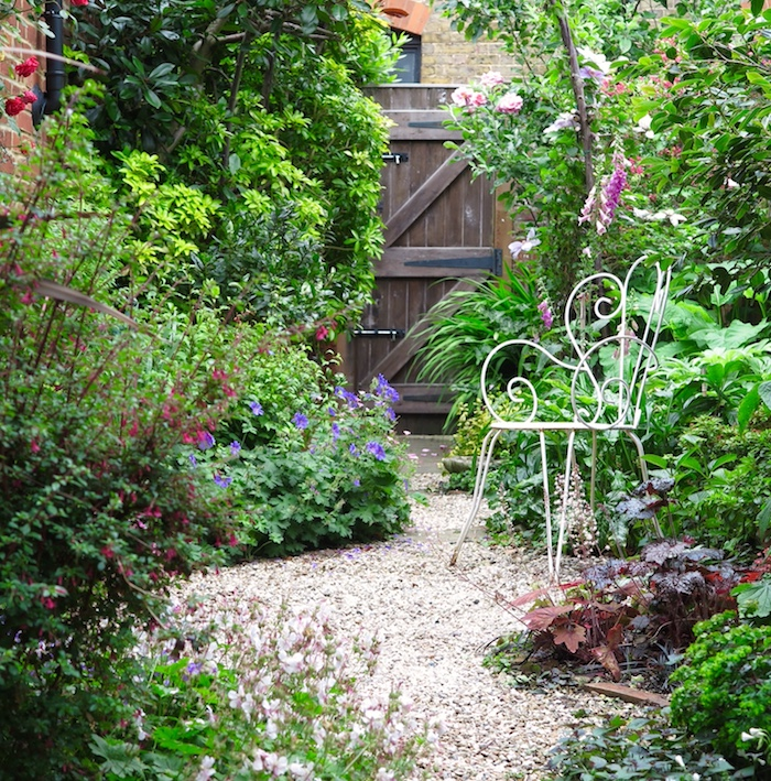 cailloux blanc, idée comment décorer son jardin, coin vert dans la cour avec porte en bois marron foncé