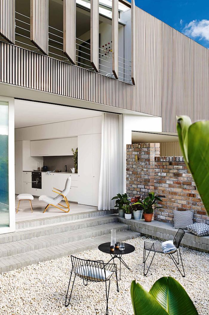 decoration exterieur, façade de maison en bois peinte taupe, coin de relax extérieur avec coussins décoratifs gris