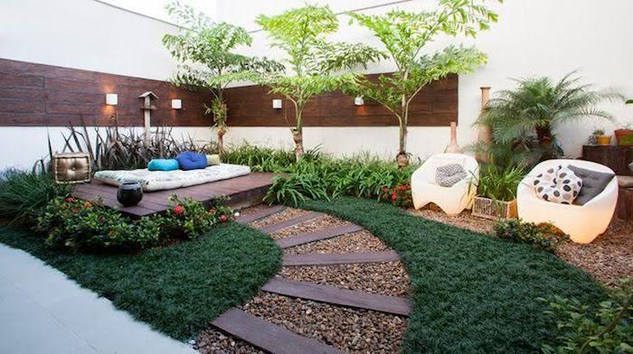 idee jardin, gazon synthétique et sentier en planches de bois marron, petits fauteuils blancs avec coussins gris