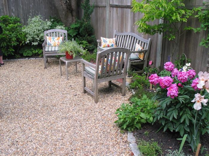 idee deco jardin, coussins décoratifs blancs à motifs feuilles multicolore, clôture de jardin en bois foncé