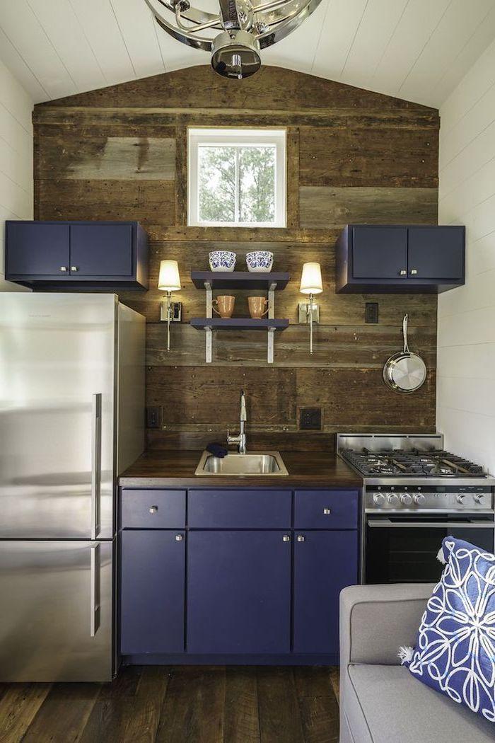 petite cuisine équipée, canapé compact en gris avec coussin décoratif à design florale bleu et blanc