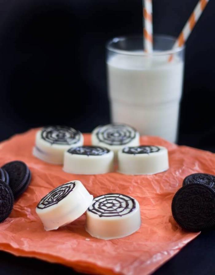 des biscuits oreo enrobés de chocolat blanc et décoré comme des toiles d'araignée, recette halloween facile et rapide pour un buffet sucré dans l'esprit de la fête