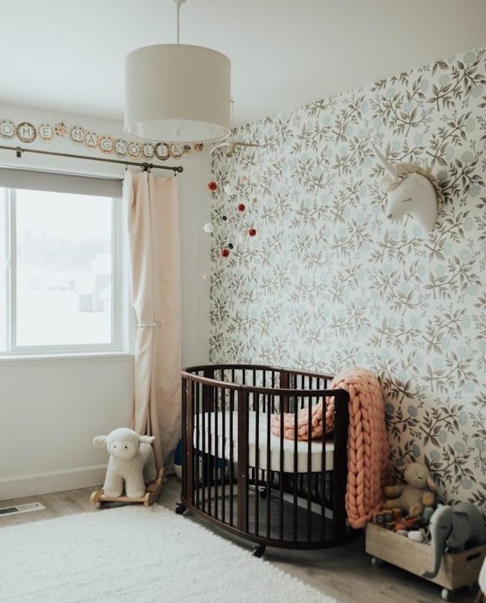 papier peint enfant, chambre bébé fille, lit bebe en bois marron à roulettes, tapis blanc, coffre bois à jouets, tapisserie, imprimé floral