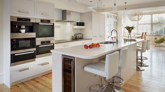 amenagement cuisine, lampes suspendues en verre, plafond et murs peints en blanc, chaises fauteuil en tissu vert