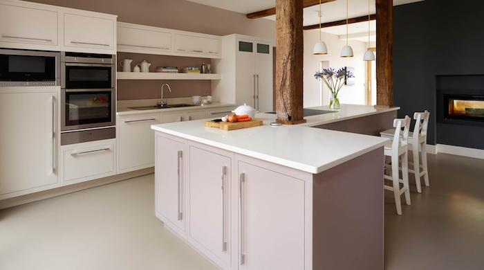 ilot central cuisine d'angle avec comptoir blanc et armoires rose pastel, cheminée moderne et noire dans la cuisine