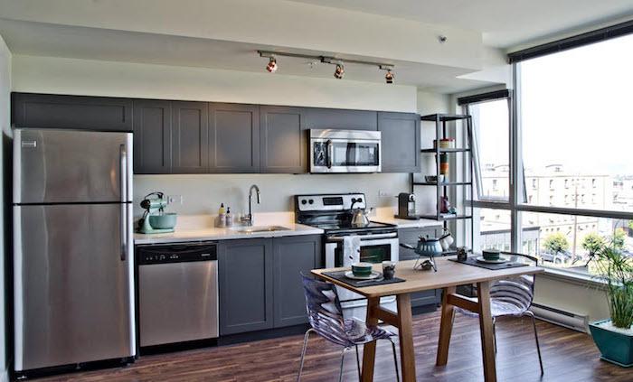 amenagement cuisine, plafond blanc et grande fenêtre dans la cuisine, table à manger en bois clair avec chaises imitation plastique transparentes