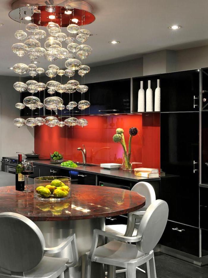 agencement cuisine, plafond blanc avec lustre guirlande en petites lampes suspendues, cuisine avec meubles noirs et crédence rouge