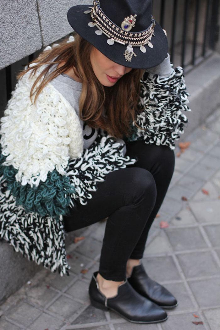 tendance chaussure en cuir noir, cheveux longs marron, gilet moelleux en blanc noir et vert