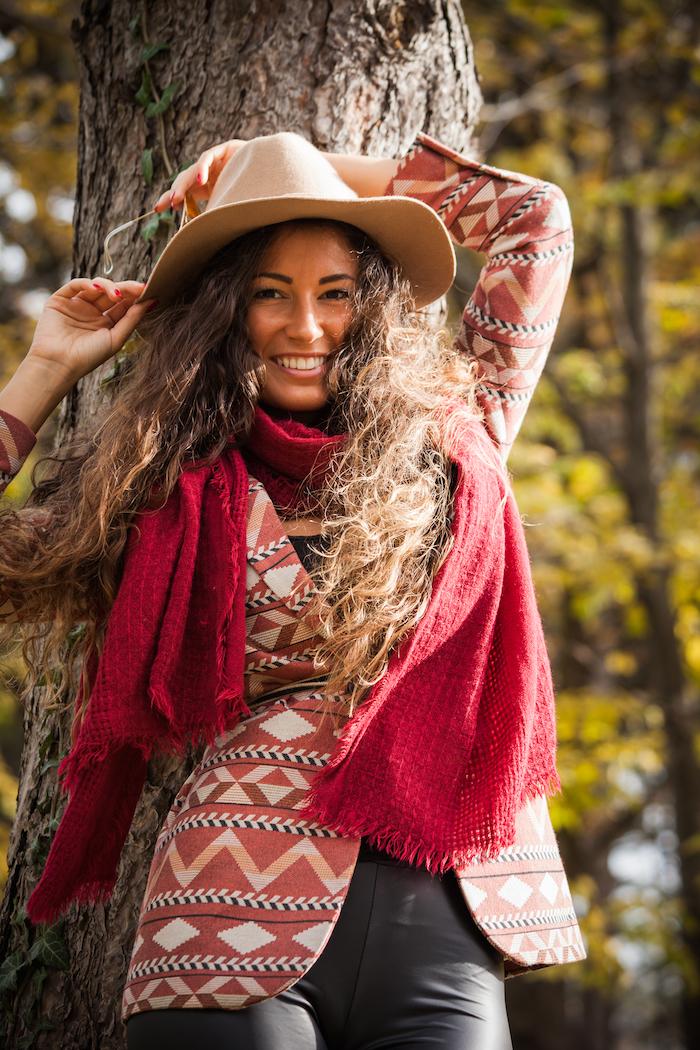 vetement femme, cheveux longs frisés marron avec capeline beige, pantalon cuir noir avec débardeur noir et blazer à motifs ethnique