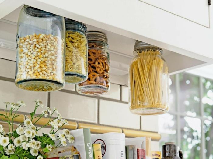 idée de rangement astucieux dans la cuisine en bocaux en verre, accrochés au fond un placard, relooker une cuisine comment faire