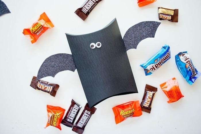 bricolage halloween avec rouleau de papier toilette, repeint en noir, des ailes en papier gris et des yeux mobiles, bonbons colorés